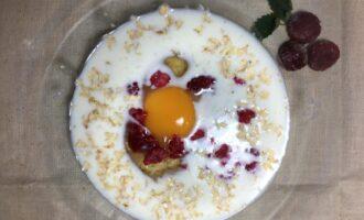 Шаг 2: Насыпьте в миску хлопья, влейте молоко, вбейте яйцо, добавьте несколько штук малины и ложку мёда.