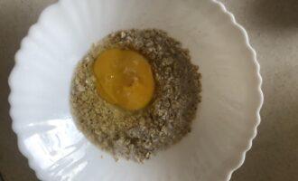 Шаг 2: В глубокую посуду к овсянке добавьте творог, яйцо и сахарозаменитель, перемешайте. Оставьте разбухать на 40 минут.