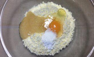 Шаг 3: Добавьте яйцо, мёд и разрыхлитель в творог и перемешайте вилкой до однородной консистенции.