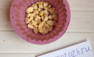 Шаг 6: Возьмите форму для выпечки (слегка смажьте форму маслом), равномерно выложите часть яблок на дно формы.