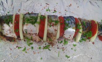 Шаг 4: Кусочки рыбы посолите, посыпьте приправой, свежей петрушкой заправьте помидором и луком. Выложите на фольгу, герметично заверните.