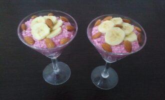 Шаг 5: Выложите творожную массу с малиной в порционные чашки, сверху уложите банан и миндаль.