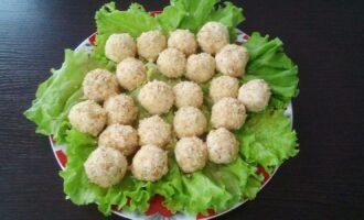 Шаг 5: Сформируйте шарики, обваляйте их в грецких орехах. Выложите на зелень или шпинат.
