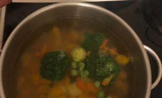Шаг 3: Кастрюлю наполните водой и поставьте на огонь. Поочередно добавляйте овощи, так, чтобы новый овощ оказывался в кастрюле после закипания предыдущего. Сначала лук, а как закипит вода - морковь, потом картофель, тыкву, и перец. Оставьте на 10 минут на медленном огне. После добавьте замороженные овощи, соль и проварите ещё 10 минут.