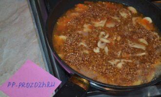 Шаг 4: Гречу промойте, добавьте в сковороду к грибам и помидору. Залейте водой 1 к 2. Если жидкость в сковороде есть, то есть вся не выпарилась, то воды лучше взять меньше. Накройте крышкой, доведите до кипения, и на самом медленном режиме готовьте около 15-20 минут.