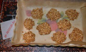 Шаг 5: Застелите противень или жаропрочное блюдо пекарской бумагой. Выкладывайте овсяную массу десертной ложкой, выравнивая в виде плоского печенья. Можно формировать колобки, но тогда чуть увеличьте время готовки. Запекайте в предварительно разогретой духовке при 180 градусах 20 минут.