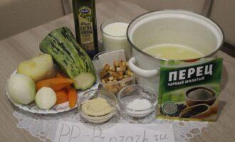 Шаг 1: Подготовьте ингредиенты: куриный бульон, кабачок, отварной картофель, отварную морковь, репчатый лук, соль, перец чёрный молотый, чеснок, гренки, молоко, оливковое масло.