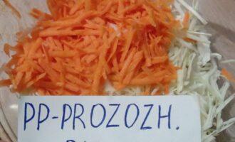 Шаг 3: Морковь натрите на средней терке. Добавьте её к капусте.