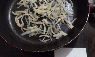 Шаг 3: Пока баклажаны пекутся, почистите лук и порежьте его полукольцами. Нагрейте сковороду с одной ложкой оливкового масла и обжарьте лук на слабом огне пару минут.