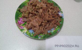 Шаг 2: Мясо отварите в течении 1,5 часов, добавив лавровый лист. Затем достаньте из бульона, отделите от кости, разберите на кусочки небольшого размера.