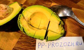 Шаг 4: Авокадо разрежьте пополам. Каждую половинку, не вынимая из кожуры, порежьте кубиками. Затем достаньте мякоть ложкой и выложите сверху на салат.
