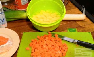 Шаг 2: Поставьте кастрюлю с водой на плиту. Пока вода будет закипать, нарежьте картофель и морковь любимым способом. Я режу кубиками. Бросьте в кипящую воду.