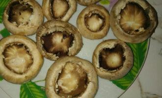 Шаг 3: Из шампиньонов извлеките ножки и немного посолите шляпки грибов внутри.