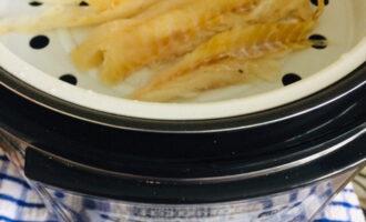 Шаг 3: В чашу мультиварки налейте воду, установите контейнер для приготовления на пару, выложите в него рыбу, посолите.