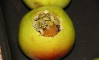 Шаг 7: Сверху положите семена тыквы и мед (по желанию). Налейте пол стакана воды в форму, чтобы яблоки не пригорели и поставьте в духовку на 20-30 минут при 180 градусах.