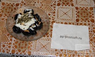 Шаг 8: Выложите чернослив, сверху полейте сметаной и посыпьте тыквенными семечками. Десерт готов.