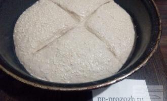 Шаг 5: После второго подъёма вымесите тесто. Сформируйте булку и положите её в смазанную маслом или обсыпанную мукой форму для расстойки. Поверхность смажьте водой и обсыпьте кунжутом. Накройте форму салфеткой.