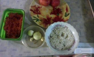 Шаг 2: Промойте рис, очистите от кожуры помидоры, лук, чеснок. Удалите семена в перце чили, помойте и почистите морковь и натирите на крупной терке. Затем налейте немного растительного масла в кастрюлю, опустите туда очищеные, порезанные помидоры и тушите 5-7 минут.
