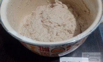 Шаг 3: Положите в кастрюлю закваску, размешайте. Добавьте просеянную муку. Засыпайте её частями, каждый раз вымешивая тесто.