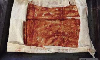 Шаг 4: На чистый и сухой противень положите лаваш, смажьте томатной пастой и сверните края.