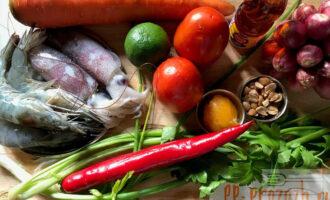 Шаг 1: Подготовьте ингредиенты: морепродукты (креветки и кальмары), овощную базу (томаты, лук-шалот, морковь), зелень (зелёный лук и сельдерей) и составляющие для заправки (мёд, рыбный соус, чили перец, лайм, жареный арахис).