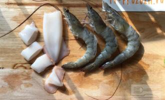 Шаг 2: Подготовьте морепродукты для дальнейшей термообработки: у кальмаров удалите внутреннюю хорду (если они неочищенные) и наружную пленку, у креветок - панцирь и кишечную вену (черная жилка по средней линии).