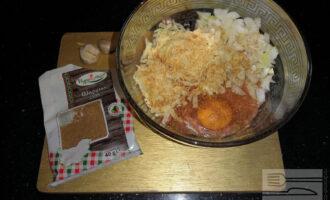 Шаг 3: Выложите фарш в подходящую по размеру чашу. Добавьте к фаршу измельченные сыр, лук, чеснок. Вбейте яйцо. Добавьте соль по вкусу.