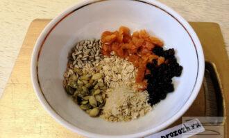 Шаг 6: Выложите в чашу все подготовленные ингредиенты: овсяные хлопья, отруби, курагу, изюм, семена подсолнечника и тыквы. Перемешайте ложкой.