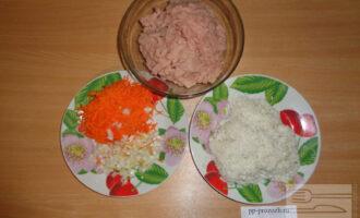 Шаг 2: Куриную грудку перекрутите на мясорубке, лук мелко нарежьте, морковь натрите на мелкой терке. Рис оварите до полуготовности.