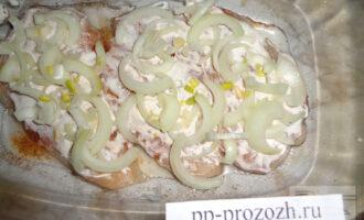 Шаг 5: Выложите мясо в форму для запекания, немного посолите и смажьте йогуртом, сверху положите лук.