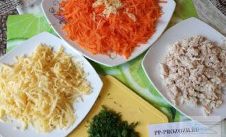Шаг 2: Сыр и морковь натрите на крупной терке, чеснок натрите на мелкой терке или пропустите через пресс и смешайте с морковью. Куриную грудку и зелень нарежьте.