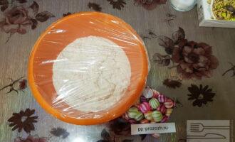 Шаг 6: Накройте миску полиэтиленовой пленкой, сверху укутайте полотенцем. Поставьте миску в теплое место на 12 часов. Тесто должно подняться, но совсем немного, поскольку не содержит дрожжей и поднимается засчёт естественного брожения.