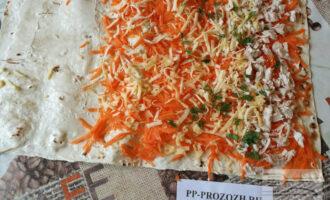 Шаг 3: Расстелите на столе один лист лаваша, смажьте его домашним майонезом, сверху разложите третью часть тертой моркови с чесноком. Распределите ее так, чтобы один край лаваша остался свободным (примерно 10 сантиметров). Вдоль противоположного края разложите треть куриного мяса, посыпьте сыром и зеленью.