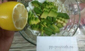 Шаг 4: Насыпьте в салатник капусту, авокадо и полейте лимонным соком. Добавьте немного цедры лимона.