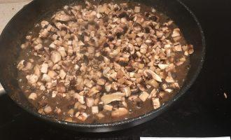 Шаг 7: Добавьте нарезанные шампиньоны в сковороду, перемешайте. Готовьте еще 5 минут.