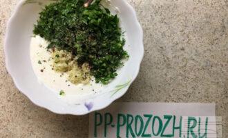Шаг 4: Приготовьте соус. Смешайте сметану, нарезанную зелень, измельченный чеснок и специи.