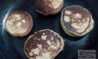 Шаг 6: Тесто увеличивается в объёме и покрывается пузырьками, его перемешивать нельзя.  Просто набирайте его ложкой и выкладывайте на разогретую сковороду.  Жарьте оладьи на смазанной маслом сковороде на среднем огне. Если покрытие антипригарное, то масло можно не использовать.