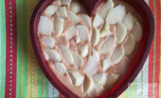 Шаг 4: Потом возьмите форму, выложите в нее нарезанный кружочками банан и залейте тестом. Нарежьте лепестками яблоко и украсьте пирог. Ставьте в предварительно прогретую духовку.
