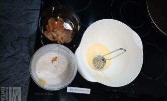 Шаг 2: Курагу промойте и залейте кипятком.  Отделите белки от желтков и добавьте желтки к йогурту.