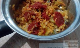 Шаг 5: Добавьте в зажарку томатную пасту, обжарьте, помешивая, одну минутку. Влейте немного воды, размешайте и готовьте минуты три.