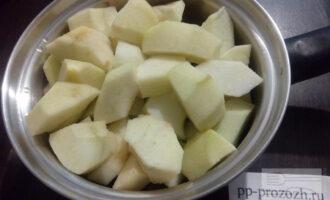 Шаг 2: Яблоки хорошо промойте, удалите семенные коробки и очистите от шкурки. Положите их в кастрюльку с толстым дном, налейте немного воды (50 миллилитров) и поставьте томиться на минимальный огонь.