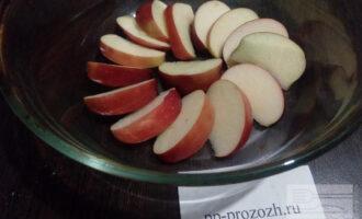 Шаг 2: Одно яблоко помойте, удалите семена и порежьте дольками. Выложите их на дно формы.
