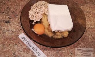 Шаг 3: К яблоку добавьте творог, овсяные хлопья и яйцо.