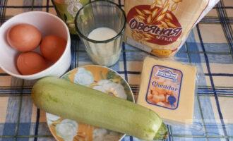 Шаг 1: Подготовьте ингредиенты: кабачок, сыр, яйца, чеснок, овсяную муку, молоко, оливковое масло.
