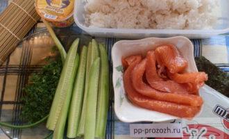 Шаг 1: Подготовьте ингредиенты: вареный рис для суши, водоросли нори, огурец, форель или семгу слабосоленую, плавленый сыр, укроп, зеленый лук. Также вам понадобится коврик для приготовления суши и роллов. Коврик застелите пищевой пленкой.