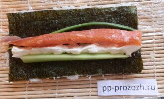 Шаг 6: Рядом с сыром плотно уложите рыбу, огурец и зеленый лук.