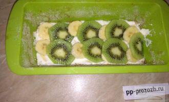 Шаг 5: Половину творога выложите в форму, затем выложите банан и киви. Сверху вылейте оставшуюся часть творога. На творог выложите несколько кусочков киви.