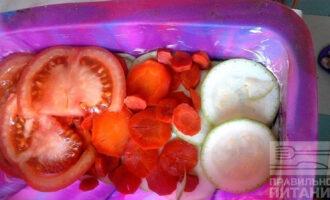 Шаг 6: На кабачок выложите морковь и томаты, нарезанные кружочками.
