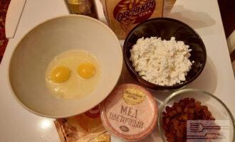 Шаг 1: Подготовьте ингредиенты: яйца, мед, овсяную муку, творог, изюм, разрыхлитель теста, ваниль, оливковое масло.
