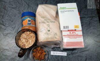 Шаг 1: Подготовьте продукты: овсяные хлопья долгой варки, цельнозерновую муку, арахисовую пасту, изюм, молоко, разрыхлитель и сахарозаменитель.